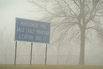 Bald Eagle Mountain sign on Route 15 with elevation sign of 1013 feet in fog and rain.