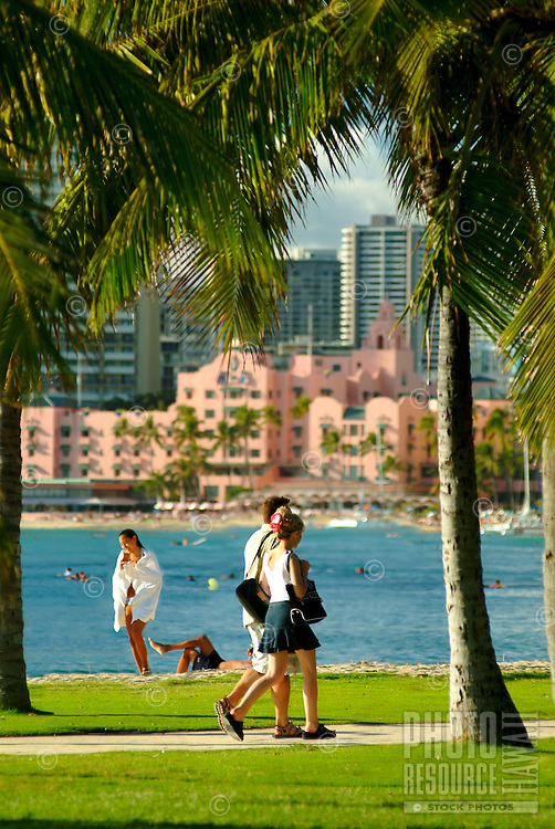 """A couple strolls along a palm tree lined path off  Waikiki Beach with the blue ocean and the Royal Hawaiian Hotel, or """"""""pink palace"""""""" in the background."""