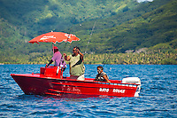Tahitians fishing from small red boat with Coca Cola umbrella