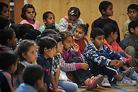 """Young children watch a performance by Roma or gypsy theater Romathan in """"Dwarf"""" at the Banske Elementary School with a Roma or gypsy majority student body in Banske, Slovakia on June 2, 2010."""