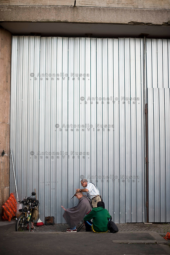 Un barbiere di strada taglia i capelli a un cittadino straniero nei pressi della Stazione Termini.<br /> Street barber at Termini Station