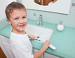 USA, Illinois, Metamora, Boy (6-7) applying toothpaste to toothbrush in bathroom
