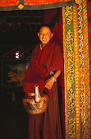 Monk carrying a kettle of butter tea, Ganden Monastery.