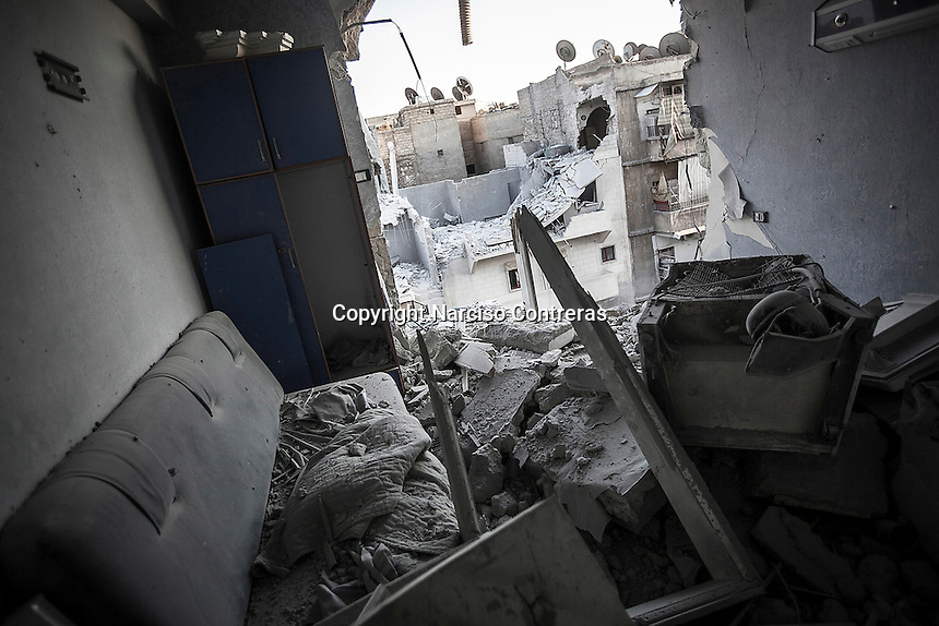 Buildings hit by a bomb explosion are showed up from a shattered room at the fifth floor of a hospital which has been targeted by aircraft shelling several times in Aleppo City.