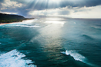 An aerial view of surfers and a huge wave under sun rays on the North Shore of O'ahu.