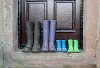 Four pairs of wellington boots, two pairs of childrens, one pair a female adult's and one pair a male adult's, outside a farmhouse door, Whitewell, Lancashire.