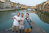 Young men taking selfies on a bridge over the Arno near the Ponte Vecchio, Florence, Italy