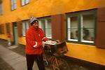 A postman delivers mail in the old Nyboder neighborhood in Copenhagen, Denmark