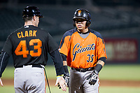 AZL Giants designated hitter Diego Rincones (35) receives a high five from first base coach Doug Clark (43) during a game against the AZL Cubs on September 6, 2017 at Sloan Park in Mesa, Arizona. AZL Giants defeated the AZL Cubs 6-5 to even up the Arizona League Championship Series at one game a piece. (Zachary Lucy/Four Seam Images)