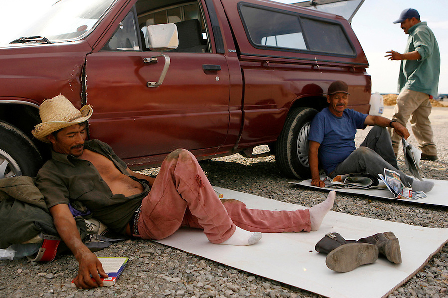 Mecca for Misery.Fernando Vargas, 48, of Mexicali, and Nicolas Garcia, 58, of Mexicali, relax after working in the vineyards outside of the area desiginated for public showers and bathrooms for farm workers. At night, the men sleep on cartons in the parking lot outside of Leon's Market in Mecca.