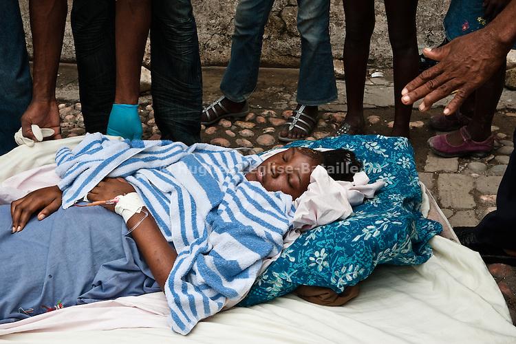 Une blessée est amenée sur un matelas dans les jardins de l'hôpital St Pierre à Jacmel (Haiti) le 19/01/2010. Partiellement détruit par le séisme du 12/01/2010, il héberge plus de 60 patients, certains atteints de gangrène faute de soins adéquats.