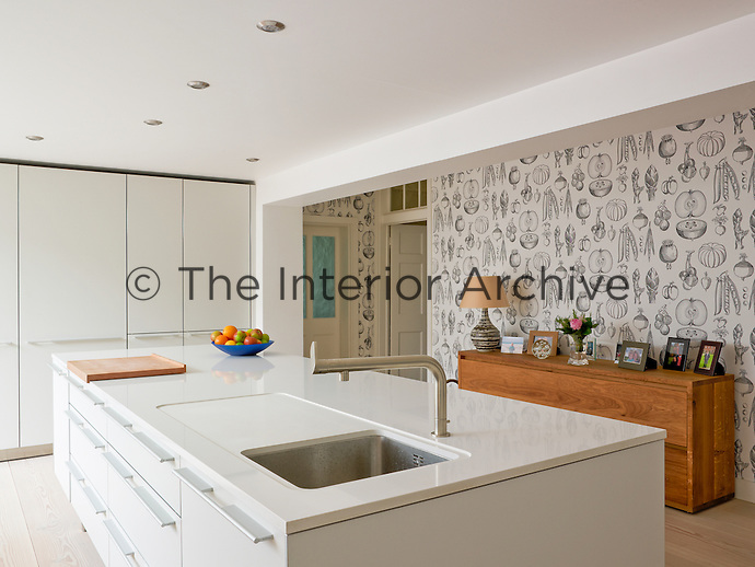 The wallpaper with a fruit and vegetable motif creates an interesting focus in the kitchen dining area