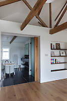 A sleek contemporary bathroom tiled in local Cornish slate is separated from the master bedroom by a sliding wooden door