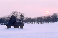 A line of trees with bare branches and a vivid winter sunset create a dramatic setting for a monumental bronze sculpture