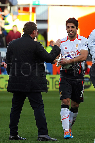 22.03.2014  Cardiff, Wales. Luis Suárez of Liverpool is the hat trick hero as he walks off the pitch with the match ball after scoring three goal during the Premier League game between Cardiff City and Liverpool from Cardiff City Stadium. Here Liverpool Manager Brendan Rodgers congratulates him