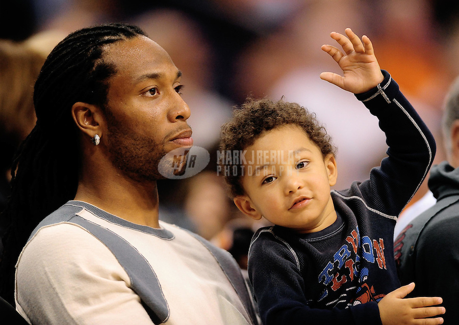Jan. 8, 2010; Phoenix, AZ, USA; Arizona Cardinals wide receiver Larry Fitzgerald sits courtside with son Devin Fitzgerald during the game between the Phoenix Suns against the Miami Heat at the US Airways Center. Mandatory Credit: Mark J. Rebilas-
