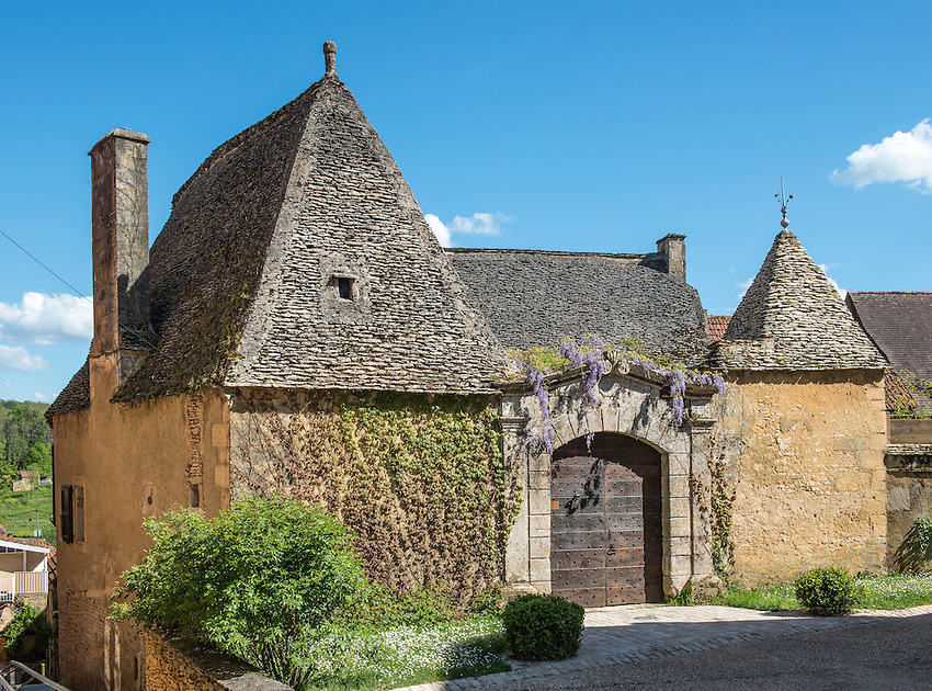 "Old house in Meyrals, Périgord, featuring ""pierres de causse"" limestone roof characteristic of the region. The stones are not cemented but are supported by a latticework of wood beams. The roof needs to be very pointed and high to support the enormous weight of the stones."