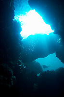 Female diver swimming past the twin openings of a large cave with sunlight shining through, Koh Ha, Thailand, Asia