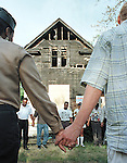 Sentinel/Dan Irving.Core city residents hold hands during a prayer vigil outside a firebombed home on Friday evening. .6/18/99