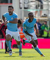 Raheem Sterling of Manchester City celebrates scoring an injury time winning goal with teammate Sergio Aguero during the Premier League match between Bournemouth and Manchester City at the Goldsands Stadium, Bournemouth, England on 26 August 2017. Photo by Andy Rowland.