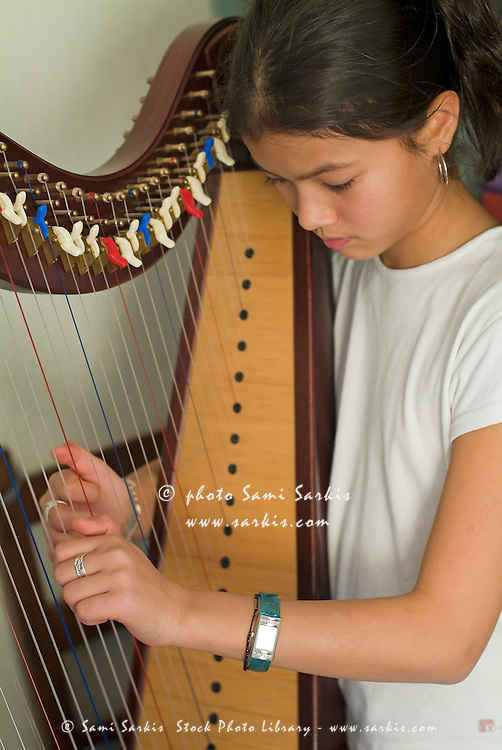 Girl practicing harp at home, France.