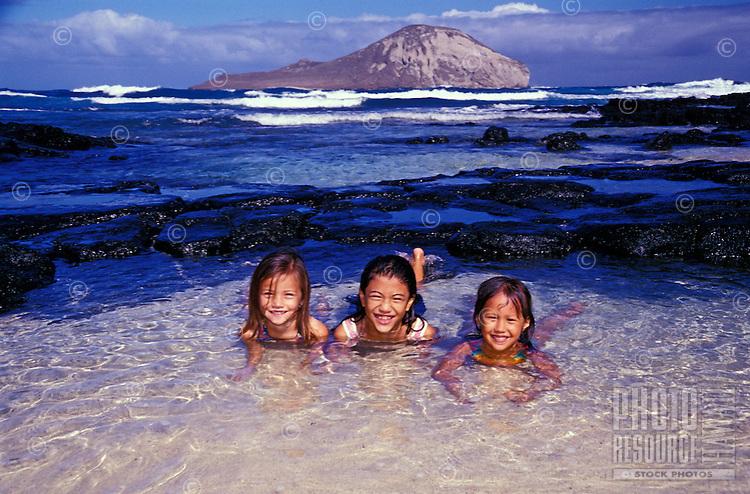 Kids in tidepools at Makapuu Beach on Oahu. Rabbit Island is in the background.
