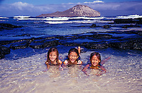 Kids in tidepools at Makapuu Beach on Oahu. Rabbit Island is in the background.