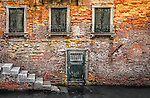 The rustic exterior facade of a building on a canal in the sestiere of Castello in Venice, Italy.
