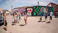 Visitors view the street art at the Welling Court Mural Project in the Astoria neighborhood of Queens in New York on Saturday, June 13, 2015. The annual neighborhood event decorates walls in this industrial part of Astoria. The project is crowd-funded and emerging street artists work side by side with established stars.  (© Richard B. Levine)