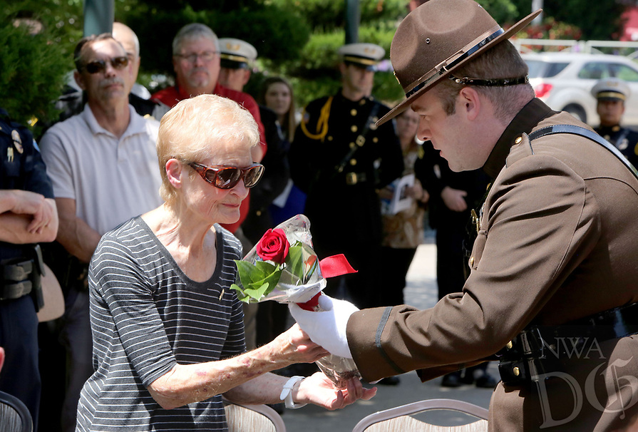 NWA Democrat-Gazette/DAVID GOTTSCHALK  Sue Hall receives a rose from Richard Bell, Law Enforcement Honor Guard, Monday, May 15, 2017, during the Northwest Arkansas Law Enforcement Memorial at the Town Center in Fayetteville. Hall's father, Elmo Ritchie, assistant chief with the Fayetteville Police Department died during service in 1968. Area law enforcement departments participated in the memorial that recognized officers from Northwest Arkansas who died in the line of duty.