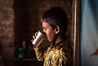 A young boy drinks water in Ambedkar Nagar in Medak, Telangana, India.