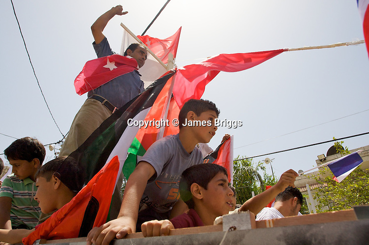 Palestinians from the village of Bil'in honour those killed during the Israeli raid on the Mavi Marmara aid ship during the villager's weekly protest against the controversial West Bank barrier, near Ramallah on 04/06/2010.