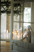A view through a door reveals a boy arranging candles around an iced cake on a large white table