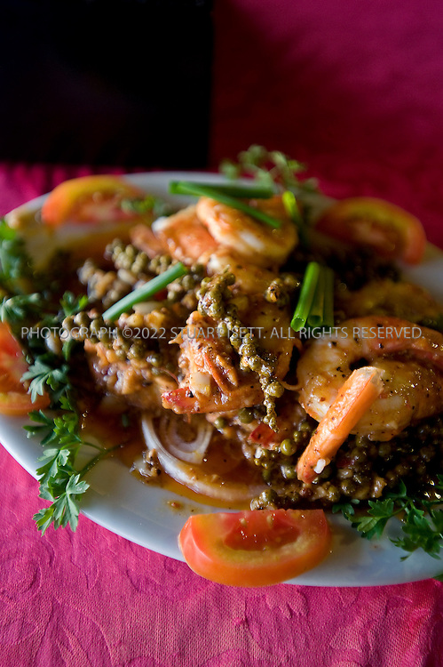 12/1/2008--Kep, Cambodia..Kim Ly's, one of the most popular seafront restaurants in Kep. Kim Ly offers not only crab and squid with green peppercorns but also traditional Khmer soups and rice dishes (entrees $3-$8), along with its wine list. 011-855-12-345-753...From the early 20th century through the 1960s, Kep was Cambodia's premier beach town, drawing weekend holiday-makers to its picturesque shores and sporting the ocean side villas of the privileged class. Nowadays, the old villas are in ruins, many of the owners killed by the Khmer Rouge. and the town is known more for its oceanfront seafood stalls than for its beaches, which are narrow and stony, offering just a few slivers of sand. For the moment at least, Kep has a real ?out of the way? feel to it - jungled mountains, empty beaches and few tourist services. The main road winds along the oceanfront, through the crab market and past small beaches and ritzy villas now crumbling in disrepair. Kep's current raison d'etre is fresh seafood, especially crab. No trip to Kep is complete without at least one seaside picnic...©2008 Stuart Isett. All rights reserved.