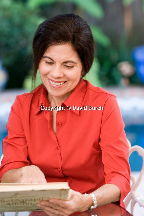 Hispanic woman smiling, looking at photo album