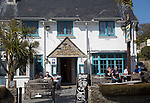 People sitting outside The Rising Sun pub, St Mawes, Cornwall, England, UK