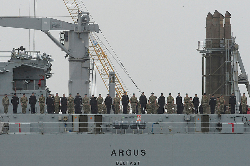 Service personal stand on the deck Royal Fleet Auxiliary Argus as it leaves Falmouth and heads towards Sierra Leone for a six month deployment to help combat the outbreak of Ebola.