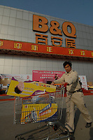 A male shopper walking with a trolley outside the B&Q warehouse and shop in Guangzhou, China. B&Q is part of Britain's Kingfisher retailing group and China's biggest chain by sales. Its foreign rivals include Sweden's IKEA and Germany's Obi. B&Q plans to open 12 new stores a year. It has doubled sales each year since it opened its first store in China in 1999. Steve Gilman, head of B&Q International, wants to have 75 stores in 30 Chinese cities by the end of 2008..29 Jan 2007