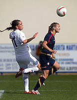 USWNT defender (2) Heather Mitts heads the ball back to the goalkeeper with Iceland's (11) Sara Bjork Gunnarsdottir close behind during the Algarve Cup.  The USWNT defeated Iceland, 1-0, at Ferreiras, Portugal.