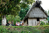BELIZE, Punta Gorda, Toledo, a family sits in front of their home on the side of the road near the Li Punit Ruins