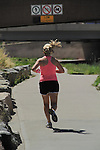 Woman running on urban trail in Denver, Colorado. .  John offers private photo tours in Denver, Boulder and throughout Colorado. Year-round Colorado photo tours.