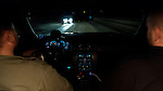 Two men drive through snowy conditions at night.