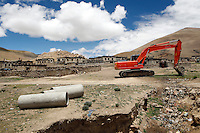"The road to Everest base camp.<br /> China started building a controversial 67-mile ""paved highway fenced with undulating guardrails"" to Mount Qomolangma, known in the west as Mount Everest, to help facilitate next year's Olympic Games torch relay./// A digger in a village on the road to EBC.<br /> Tibet, China.<br /> July, 2007"