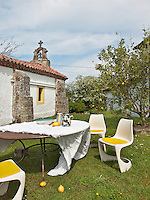 A wrought iron table and white plastic chairs are set out in a rustic garden with lemon trees.