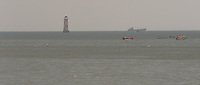 Sunk Rock lighthouse stands sentinel in the outer harbour of the Port of Mumbai, India.