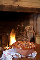 A traditional French cassoulet sitting on the table in front of a roaring fire