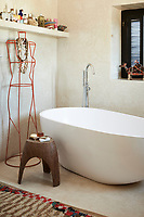 A modern stylish, free-standing bath tub stands in the centre of the tadelakt bathroom.