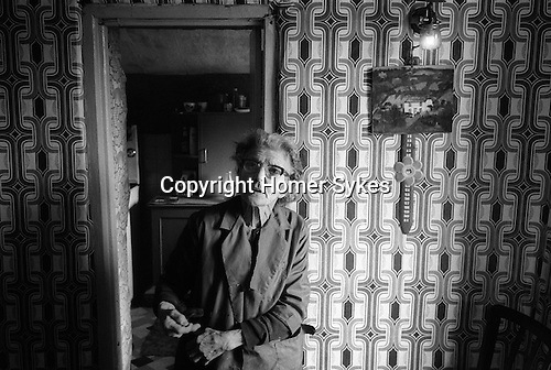 Tin Mining Cornwall 1978. Woman in her farm cottage with painting of her home under the gas light. She farms surrounded by the tin mines.