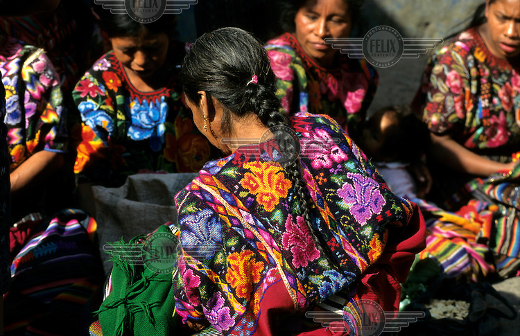 Maya women wearing huipil (traditional woven and embroidered cotton blouses) that are designed according to their village traditions at the Sunday market.