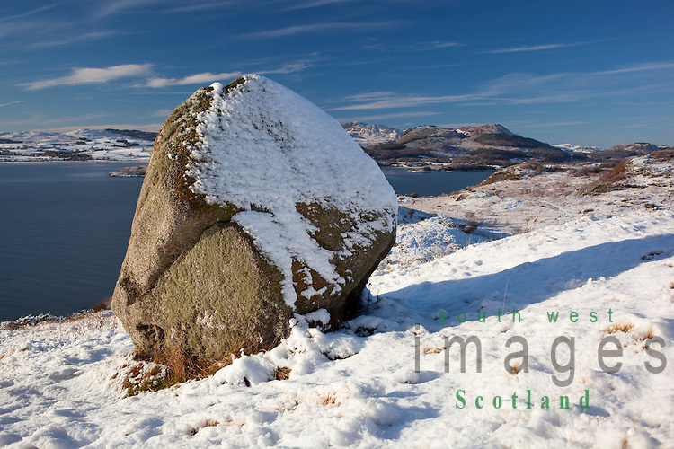 Scenic winter snow landscape erratic granite boulder sitting on the Moyl at Almorness Point looking across Orchardton Bay to Screel Hill Galloway Scotland UK